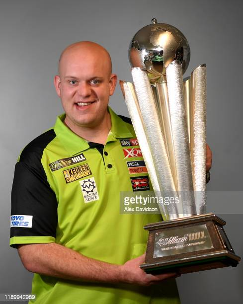 Michael van Gerwen poses with the William Hill World Darts Championship trophy during a Media Opportunity for the William Hill World Darts...