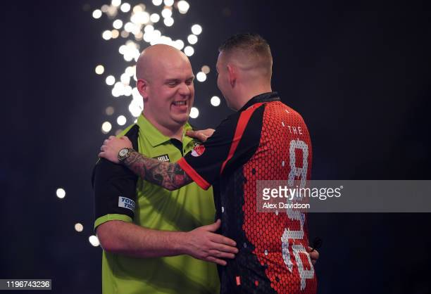 Michael van Gerwen shakes hands with Nathan Aspinall after victory in the Semi-Final match between Michael van Gerwen and Nathan Aspinall on Day 15...
