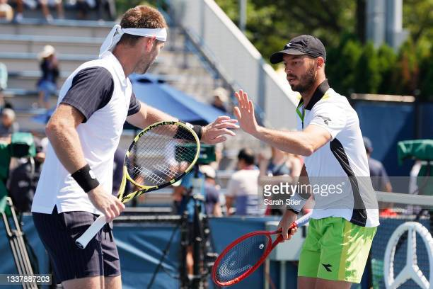 Michael Venus of New Zealand, left, high fives doubles partner Tim Puetz of Germany during their Men's Doubles first round match against Emil...