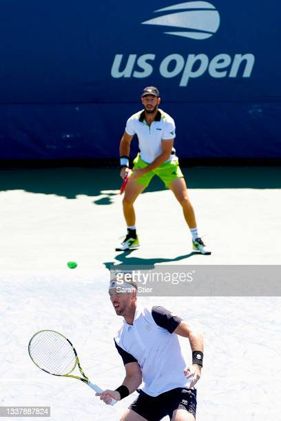 Michael Venus of New Zealand, left, returns the ball as doubles partner Tim Puetz of Germany looks on during their Men's Doubles first round match...