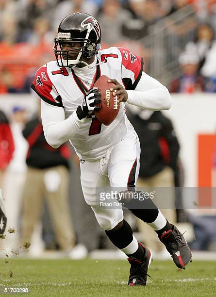Michael Vick of the Atlanta Falcons looks to pass on a scramble against the Denver Broncos on October 31, 2004 at Invesco Field at Mile High Stadium...