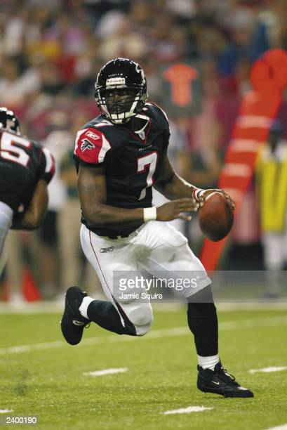 Michael Vick of the Atlanta Falcons scrambles against the Green Bay Packers on August 9, 2003 at the Georgia Dome in Atlanta, Georgia. The Packers...
