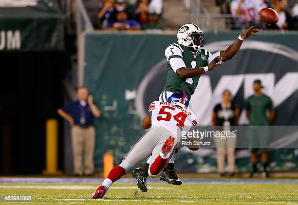 Michael Vick of the New York Jets passes the ball away from Spencer Paysinger of the New York Giants during the third quarter of a preseason game at...