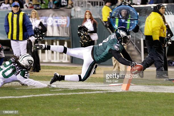 Michael Vick of the Philadelphia Eagles jumps into the end zone in front of Kyle Wilson of the New York Jets for a touchdown during the first half at...
