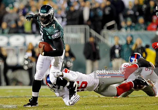 Michael Vick of the Philadelphia Eagles runs with the ball against Antrel Rolle of the New York Giants at Lincoln Financial Field on November 21,...