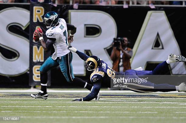 Michael Vick of the Philadelphia Eagles scrambles as Chris Long of the St Louis Rams dives for him at the Edward Jones Dome on September 11 2011 in...