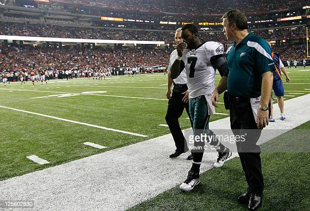Michael Vick of the Philadelphia Eagles walks off the field with trainers after being injured in the third quarter against the Atlanta Falcons at...