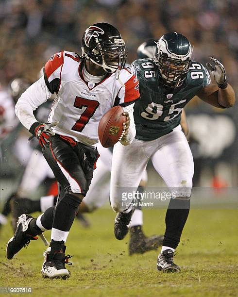 Michael Vick scrambles out of the pocket as Eagles defensive end Jerome McDougle pursues during the game between the Atlanta Falcons and the...