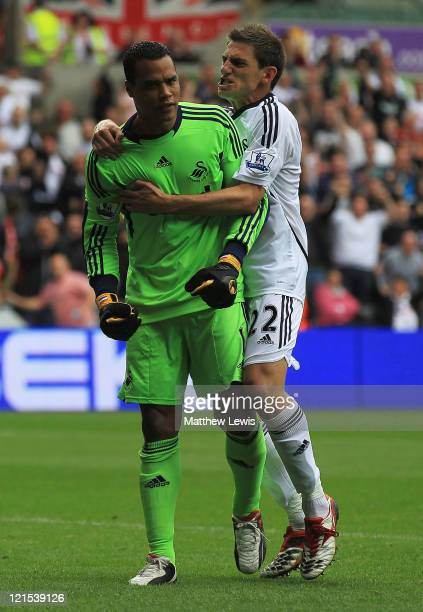 Michael Vorm of Swansea City is congratulated by Angel Rangel after saving the penalty kick from Ben Watson of Wigan during the Barclays Premier...