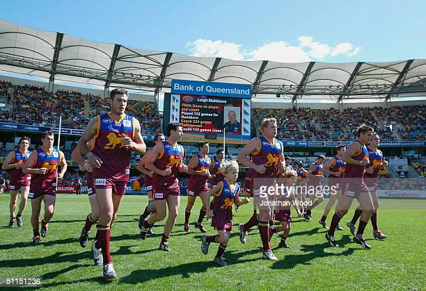 Michael Voss of the Lions leads the team onto the field before the AFL match between the Brisbane Lions and West Coast Eagles at the Gabba August 8...