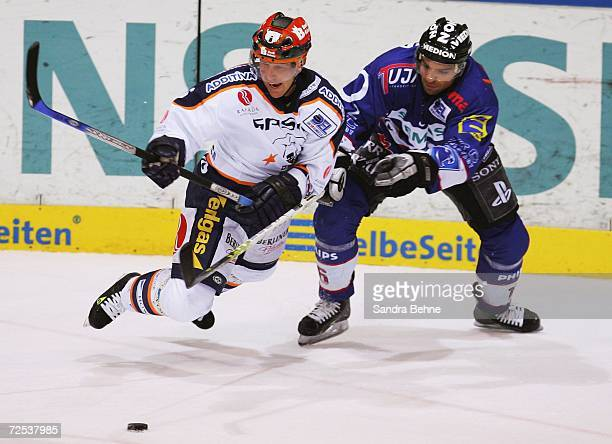 Michael Waginger of Ingolstadt challenges Andy Roach of Eisbaeren Berlin during the DEL Bundesliga game between ERC Ingolstadt and Eisbaeren Berlin...