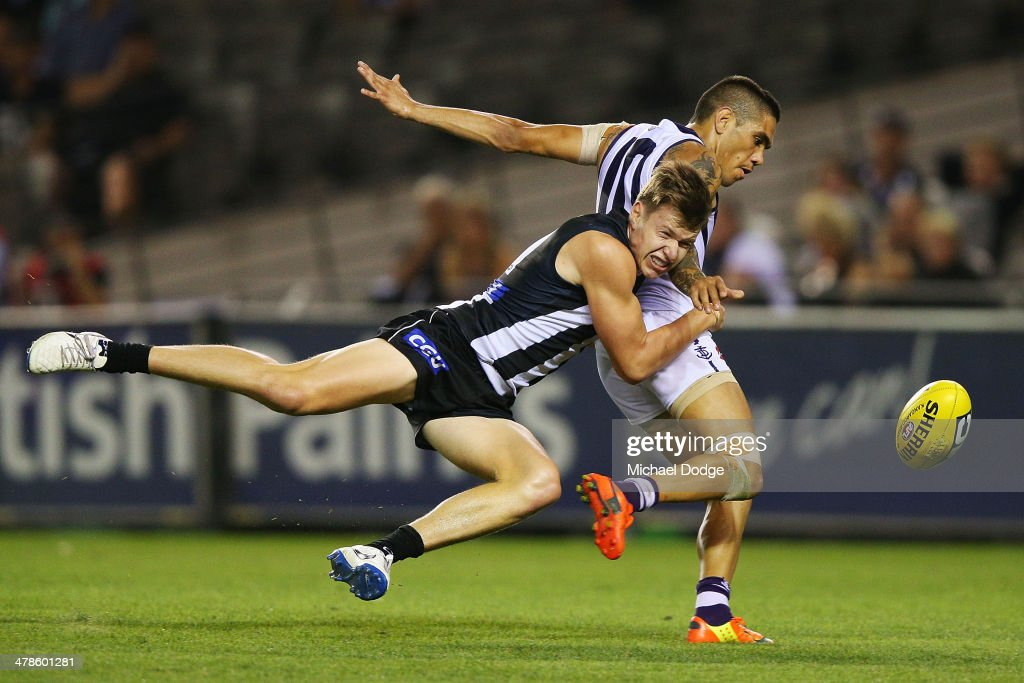 Michael Walters of the Dockers celebrates a goal as Tom Langdon of the Magpies tackles during the round one AFL match between the Collingwood Magpies and the Fremantle Dockers at Etihad Stadium on March 14, 2014 in Melbourne, Australia.