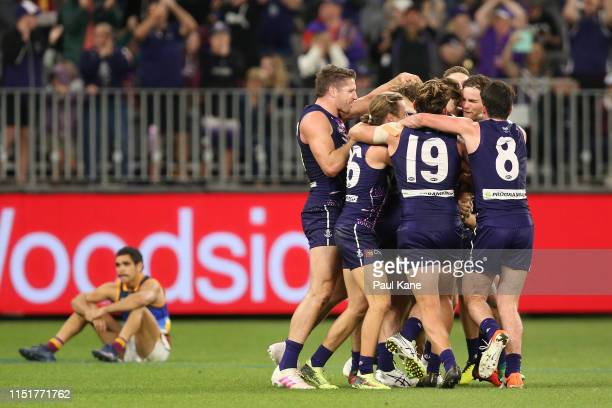 Michael Walters of the Dockers is congratulated by team mates after kicking a point to win the game during the round 10 AFL match between the...