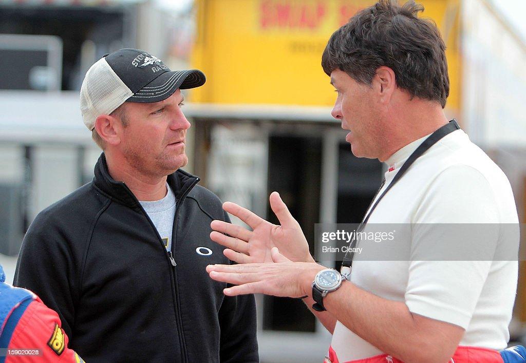 Michael Waltrip (R) and Clint Bowyer talk in the paddock during preseason testing at Daytona International Speedway on January 5, 2013 in Daytona Beach, Florida.