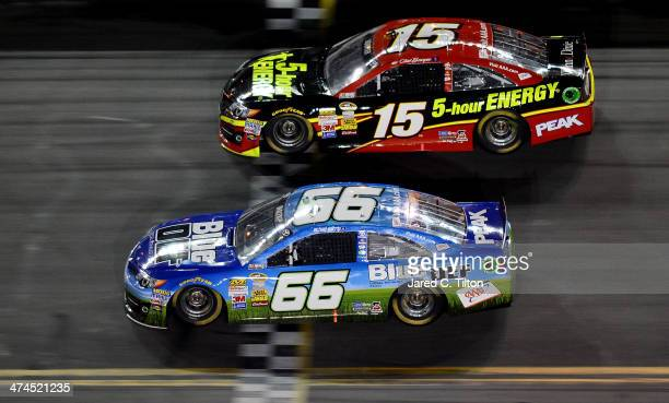 Michael Waltrip, driver of the BlueDEF/AAA Toyota, races Clint Bowyer, driver of the 5-hour ENERGY Toyota, during the NASCAR Sprint Cup Series...