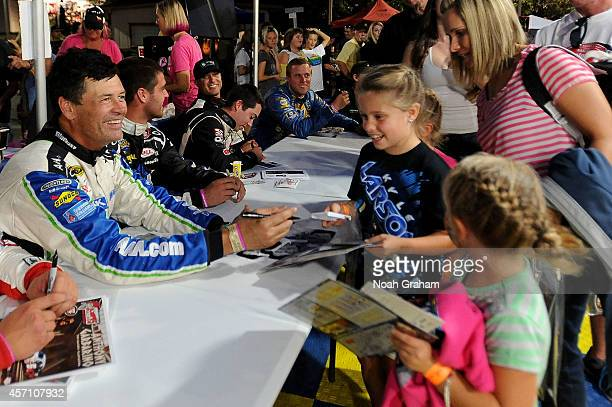 Michael Waltrip driver of the Green Toyota signs an autograph prior to the NASCAR KN Toyota/NAPA Auto Parts 150 at the All American Speedway on...