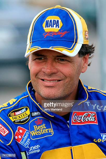 Michael Waltrip, driver of the NAPA Toyota, smiles while standing on pit road during qualifying for the NASCAR Nextel Cup Series Dodge Avenger 500 on...