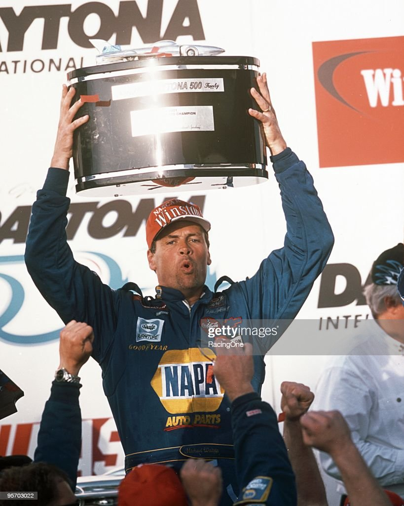 Michael Waltrip hoists the Harley J. Earl Daytona 500 trophy into the air after defeating his teammate, Dale Earnhardt Jr., in the Daytona 500. It was Waltrip's first NASCAR Cup Series triumph and first outing for DEI.