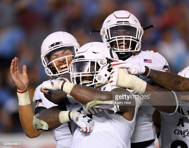 Michael Warren II of the Cincinnati Bearcats celebrates his third touchdown of the game with Kahlil Lewis and Arquon Bush to take a 2617 lead over...