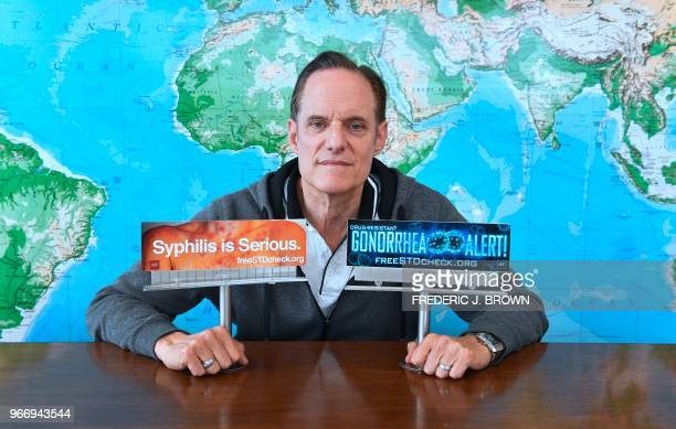 Michael Weinstein president of the AIDS Healthcare Foundation displays models of billboards which ran in Los Angeles earlier this year but have been...
