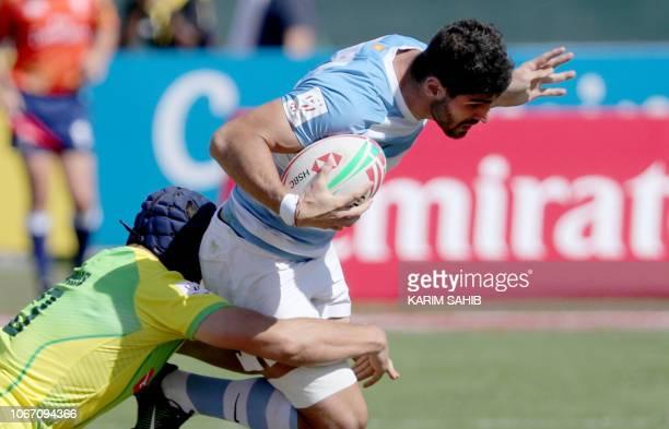 Michael Wells of Australia tackles German Schultz of Argentina during the Men's Sevens World Rugby Dubai Series Cup Quarter Final match Australia vs...