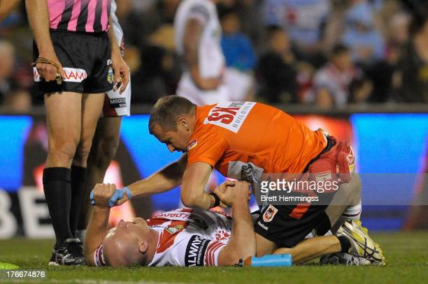 Michael Weyman of the Dragons receives treatment for a neck injury during the round 23 NRL match between the St George Illawarra Dragons and the...