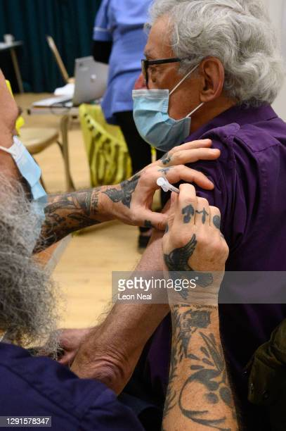 Michael Whyman receives an injection from a paramedic at a COVID-19 vaccination centre on December 16, 2020 in Chertsey, England. Chertsey Hall is...