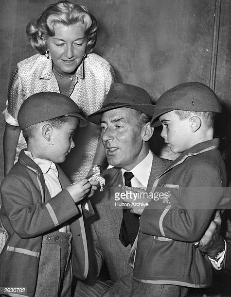 Michael Wilding British actor and leading man of the 40s is pictured with his wife and two sons saying goodbye at London Airport The two boys are his...