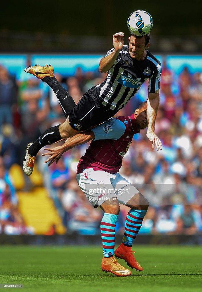 Michael Williamson of Newcastle United wins a header with Gabriel Agbonlahor of Aston Villa during the Barclays Premier League match between Aston Villa and Newcastle United at Villa Park on August 23, 2014 in Birmingham, England.