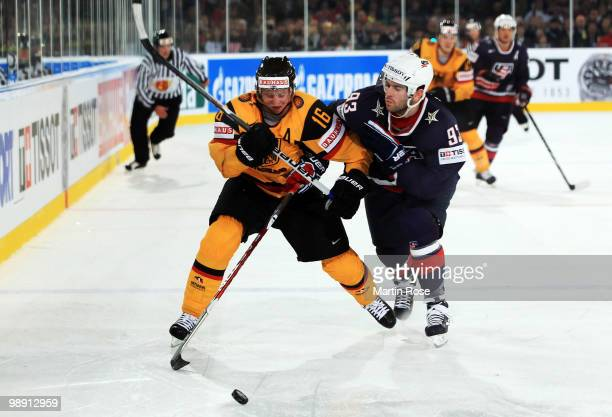 Michael Wolf of Germany and Keith Yandle of USA compete for the puck during the IIHF World Championship group D match between USA and Germany at...