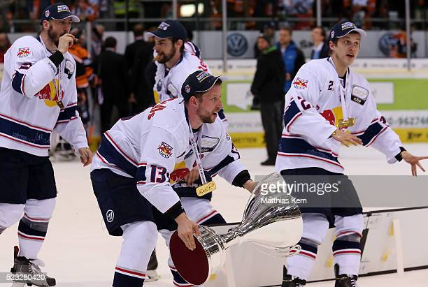 Michael Wolf of Muenchen and his team mates celebrate with the trophy after winning the DEL playoffs final game four between Grizzlys Wolfsburg and...