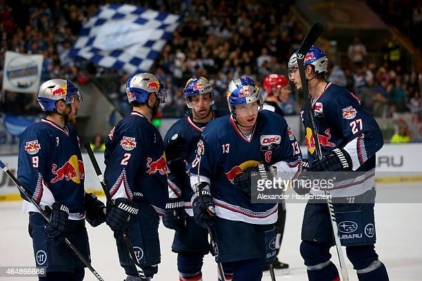 Michael Wolf of Muenchen celebrates scoring the 4th team goal with his team mates during the DEL Ice Hockey match between EHC Red Bull Muenchen and...
