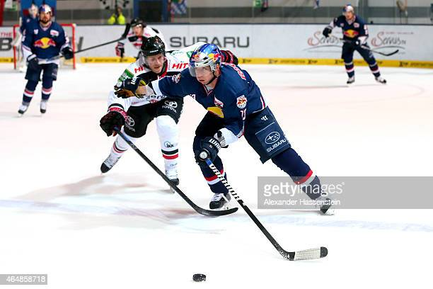 Michael Wolf of Muenchen is challenge by Andreas Falk of Koeln during the DEL Ice Hockey match between EHC Red Bull Muenchen and Koelner Haie at...