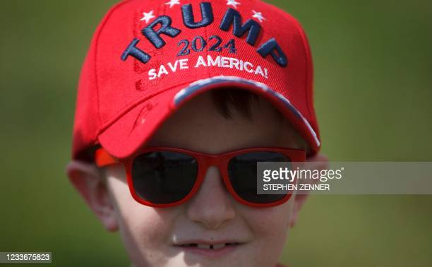 """Michael Yoder of Polk, Ohio, wears a """"Trump 2024 - Save America"""" hat during a Trump campaign-style rally in Wellington, Ohio, June 26, 2021. - Donald..."""