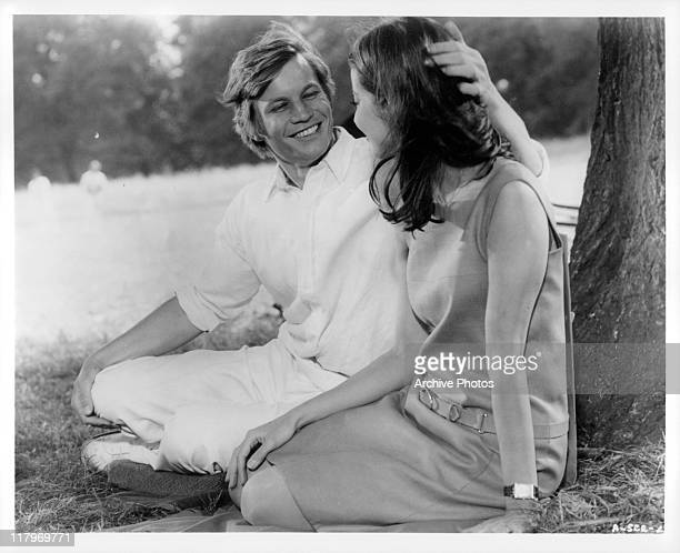 Michael York and Jacqueline Sassard sitting under a tree in a scene from the film 'Accident' 1967
