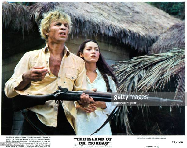 Michael York holds a gun with Barbara Carrera in a scene from the film 'The Island Of Dr Moreau' 1977