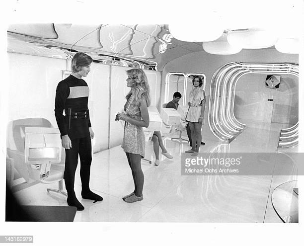 Michael York talking to Farrah Fawcett as Jenny Agutter watches in a scene from the film 'Logan's Run' 1976