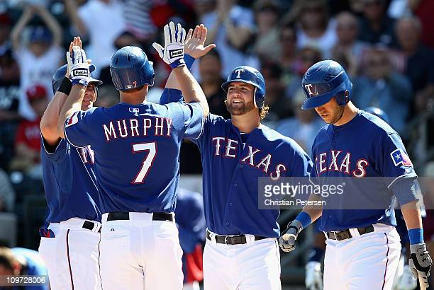 Michael Young and Mike Napoli of the Texas Rangers high-five teammate David Murphy after Murphy hit a 3 run home run against the Los Angeles Angels...