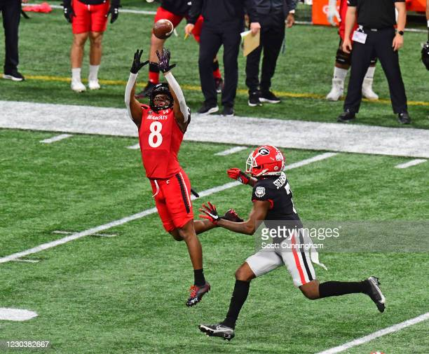 Michael Young, Jr. #8 of the Cincinnati Bearcats makes a catch against Tyrique Stephenson of the Georgia Bulldogs during Chick-fil-A Peach Bowl at...