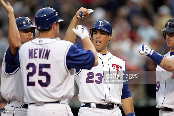 Michael Young Mark Teixeira and Hank Blalock of the Texas Rangers slap hands with Phil Nevin after hitting a three run home run against the Boston...