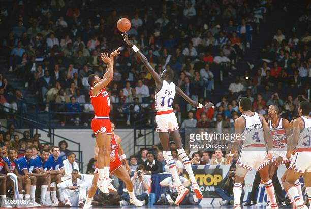 Michael Young of the Philadelphia 76ers shoots over Manute Bol of the Washington Bullets during an NBA basketball game circa 1986 at the Capital...