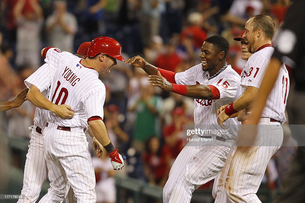 Michael Young #10 of the Philadelphia Phillies is mobbed by John Mayberry Jr. #15 and Erik Kratz #31 after singling in the winning run in the ninth inning during a game against the Colorado Rockies at Citizens Bank Park on August 21, 2013 in Philadelphia, Pennsylvania. The Phillies won 4-3.