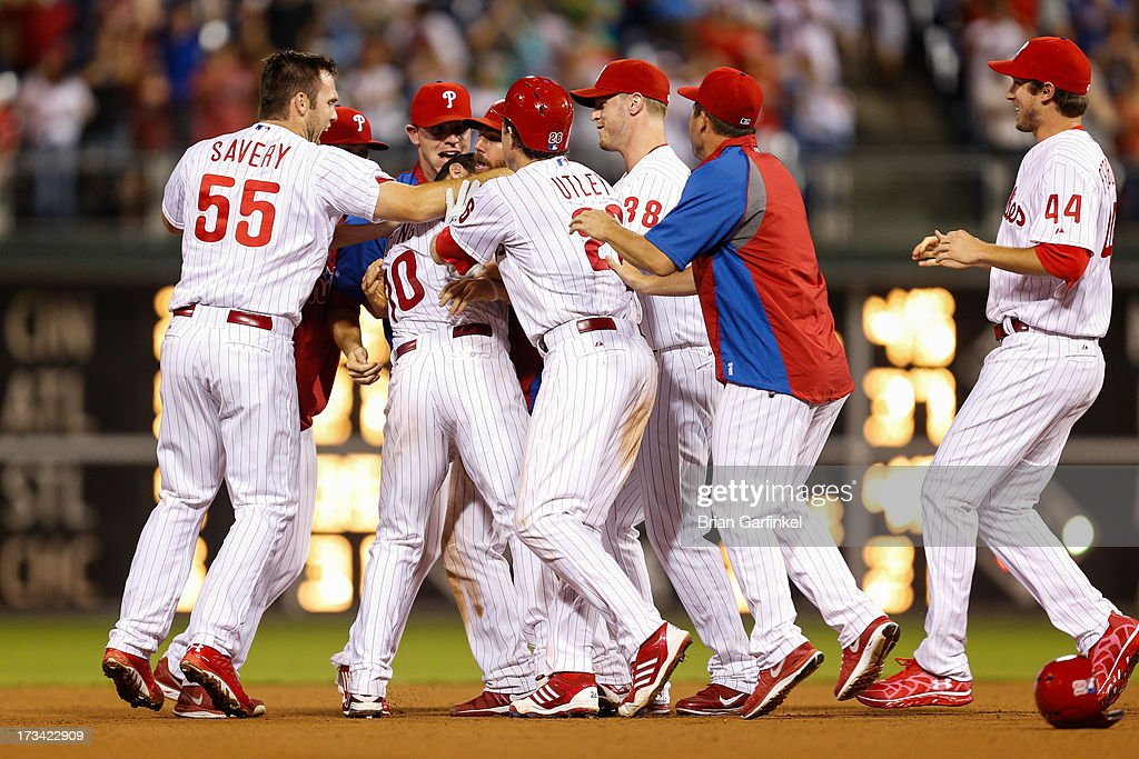 Michael Young #10 of the Philadelphia Phillies is swarmed by teammates after hitting a one-run double in the thirteenth inning to win the second game of a double header against the Chicago White Sox at Citizens Bank Park on July 14, 2013 in Philadelphia, Pennsylvania. The Phillies won 2-1 in the thirteenth inning.