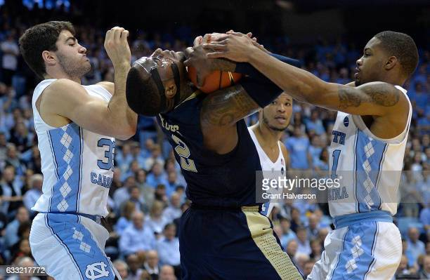 Michael Young of the Pittsburgh Panthers ties up with Luke Maye and Seventh Woods of the North Carolina Tar Heels of the North Carolina Tar Heels...