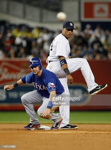 Michael Young of the Texas Rangers is forced out as Robinson Cano of the New York Yankees attempts to complete a double play on June 14 2011 at...