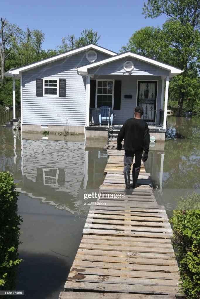 Michael Young walks to his home which is surrounded by floodwater May 6, 2011 in Tiptonville, Tennessee. Heavy rains have left the ground saturated, rivers swollen, and has caused widespread flooding in Missouri, Tennessee, Illinois, Kentucky and Arkansas.
