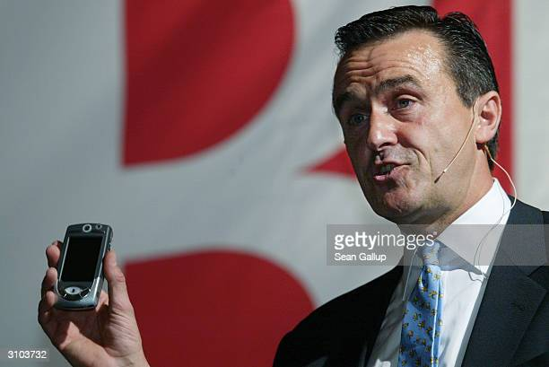 Michael Zafirovski, President and Chief Operating Officer of Motorola, holds a Motorola UMTS-capable phone while speaking at the ICT World...