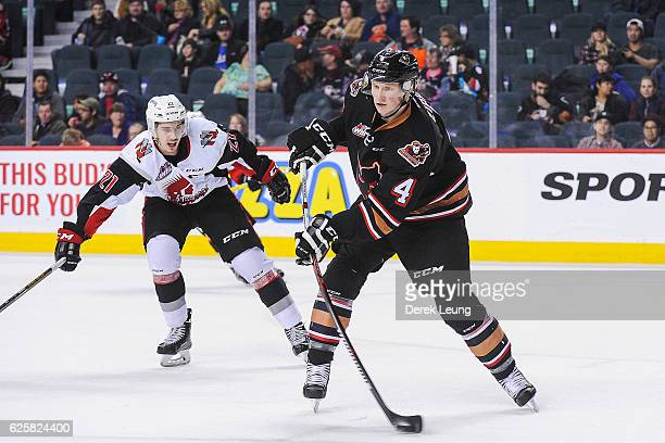 Michael Zipp of the Calgary Hitmen passes the puck up before Brett Howden of the Moose Jaw Warriors can check him during a WHL game at Scotiabank...