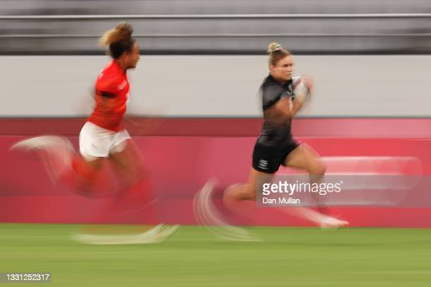 Michaela Blyde of Team New Zealand breaks away to score a try under pressure from Celia Quansah of Team Great Britain in the Women's pool A match...