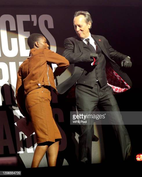 Michaela Coel and Richard E Grant greet each other with an elbow bump on stage at the annual Prince's Trust And TK Maxx Homesense Awards at London...